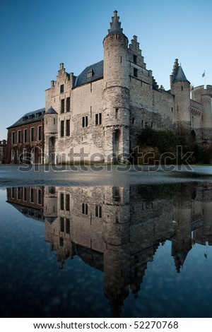 The former royal residence on the Scheldt River, the corner of Het Steen castle is beautifully reflected in a puddle of rain water on a clear blue sky day in Antwerp, Belgium. Vertical copy space