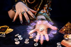 The fortune teller holds a rune with a luminous astrological circle above it in the palm of her hand. The concept of divination, astrology and predicting the future.