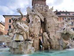 The Fountain of the Four Rivers at Piazza Navona.It was designed by Gian Lorenzo Bernini .The base of the fountain is a basin from the centre of which travertine rocks rise to support four river gods.