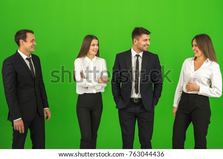 The four business people stand on the green background stock photo