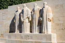 The four statues at the center of the Reformation Wall in the Parc des Bastions in Geneva, Switzerland, representing John Calvin and the Calvinism's main proponents, on a sunny summer day.