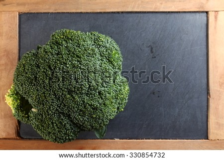 The fresh broccoli put on the slate board background represent the food and vegetable concept related idea.