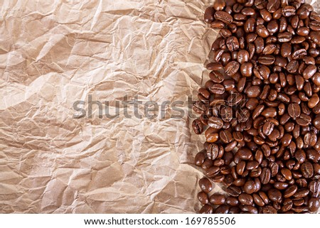 the fried beans of coffee on a crushed paper  background