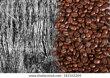 the fried beans of coffee on a wood background