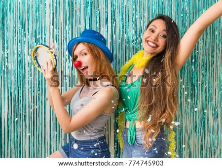The friends are dressed for Carnaval. Blue background. Women dance samba and play tambourine. #774745903