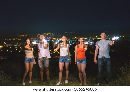 The friends hold firework sticks on a city lights background. evening night time