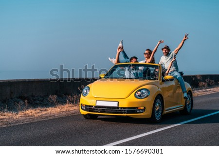 The friends travel by a cabriolet