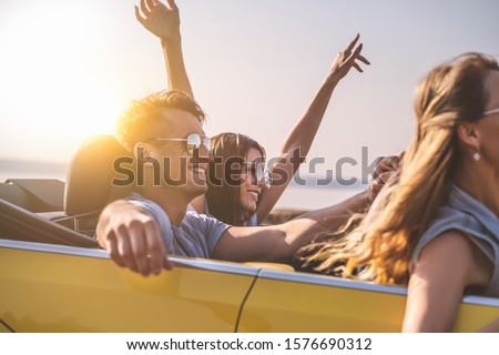 The friends travel in a yellow cabriolet
