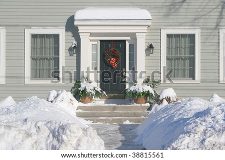 The front door of a residential family home decorated with a Christmas wreath.