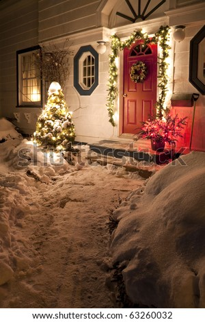 The front door of a snow covered family home decorated for Christmas.