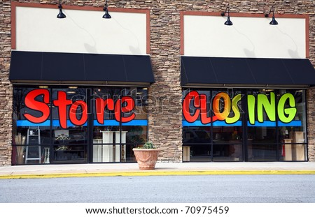 "The front of a store that is going out of business. The words ""Store Closing"" are painted on the windows."