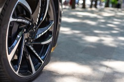 The front of the sports car. Wheel of a sports car on the background of a blurred sidewalk in a trendy metropolis area. Sports Car Alloy Wheel.