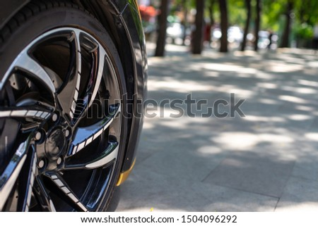 The front of the sports car. Wheel of a sports car on the background of a blurred sidewalk in a trendy metropolis area. Sports Car Alloy Wheel. #1504096292