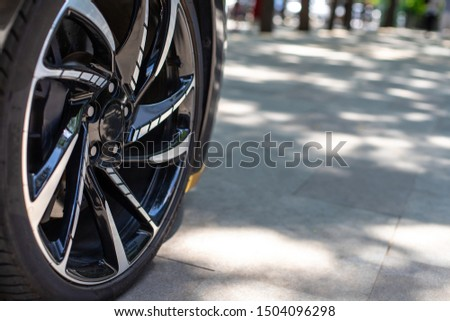 The front of the sports car. Wheel of a sports car on the background of a blurred sidewalk in a trendy metropolis area. Sports Car Alloy Wheel. #1504096298