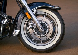 The front tire of a parked custom motorcycle.