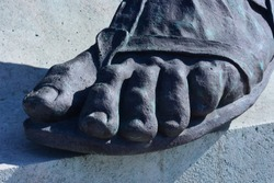 The front view close up detail of ancient man statue on a pedestal with feet toes wearing sandals in Budapest, Hungary
