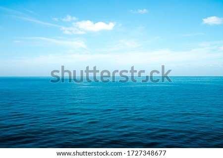 The front view in the morning sky is bright blue with clear white clouds. And the ocean deep indigo in daylight. Feeling calm, cool, relaxing. The idea for cold background and copy space on the top. Foto stock ©