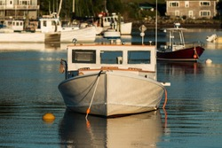 The front view of a white wooden boat with brown trim, moored in Bass Harbor Maine at dusk.