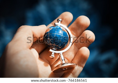The front view of Man hand is holding small globe outdoor. Concept of travelling and adventure, blur background. Fake #766186561