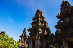 The front view of Pura Goa Lawah or Bat Cave Temple in Tulamben, Bali, Indonesia showing Balinese art on gapura or gate structure on blue sky