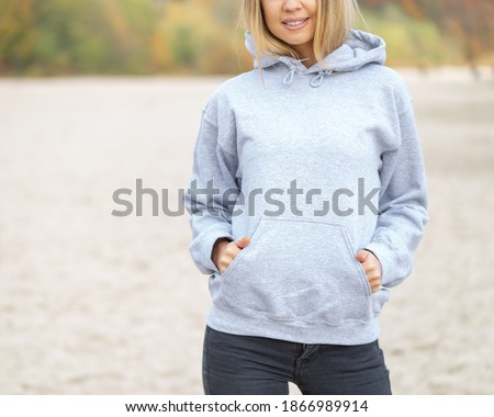 The front view of unrecognizable woman wearing light grey hoodie. She stands on the beach. Copy space on empty area on her blouse for design or inscription. Fashion mockup. Sweatshirt template. Foto stock ©