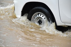 The front wheel of the pickup car was passing the urban road which fulled of floodwater during the heavy raining day. (Selective focus)