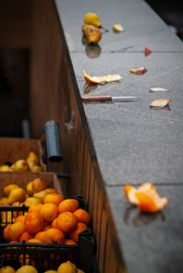 The fruit vendor's small citrus peeler lies on a smooth, flat, wet surface