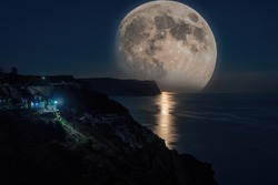 The full moon rises in a starry night sky over the sea and rocky cliffs. The concept of calmness, silence and unity with nature.