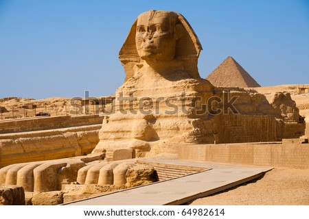 The full profile including head, feet and entire body of the Great Sphinx with the pyramid of Menkaure in the background in Giza, Egypt with nobody in frame. Horizontal copy space