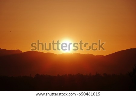 The full sun ball has just come up from behind the Cascade Mountains in western Washington. The sun glow has turned the sky bright orange. The mountains & evergreen forest in foreground are silhouette