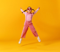 the funny child girl in pink clothes on yellow background