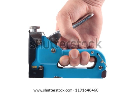 The furniture stapler in a man's hand