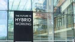 The Future is Hybrid working sign in front of a modern office building