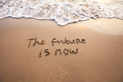 the future is now, innovative technology concept text written on sand