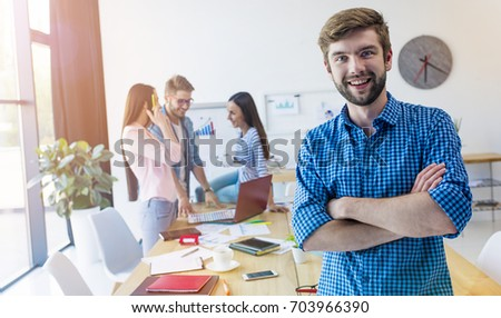 The future is ours. Cute smiling young businessman looking into the camera with his arms crossed. Modern business team. #703966390