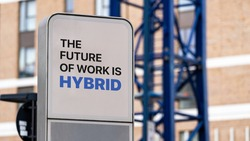 The Future of Work is Hybrid sign in a city setting under construction