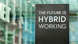 The Future of Work is Hybrid sign in front of a modern office building