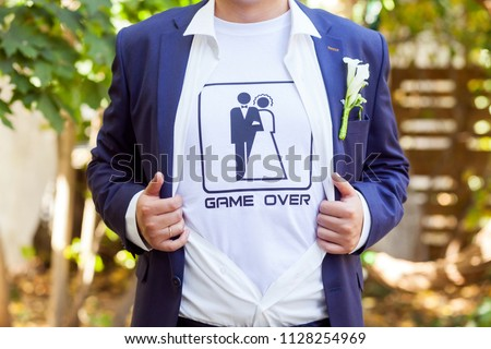 The game is over! newlywed in blue costume with opened shirt showing t-shirt with funny picture of marrieds