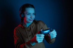 The gamer beautiful woman with headphone and joystick playing video games on dark blue background. Neon colored. Using modern technology.