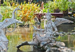 The Gandharvas in Thai style which mixed between woman, bird and fish made from cement and decorated by tile on the water