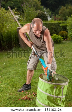 The gardener is filling the trash with some leaves.