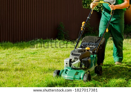 the gardener man mowing lawn with push mower.  A lawn mower is cutting green grass,  with a lawn mower is working in the backyard. Lawn mower  equipment, mowing, gardener, care, work, tool