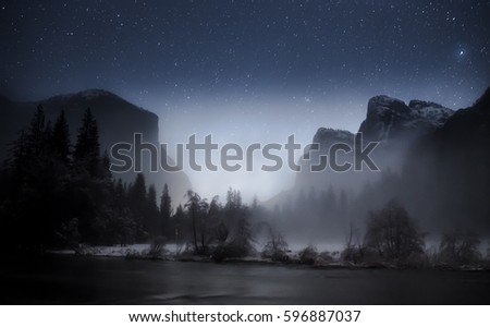 The Gates to Yosemite Valley View in January after a snowfall. The moon is rising between El Capital and Cathedral Rock causing it to glow and the valley floor is covered in a foggy mist over river.