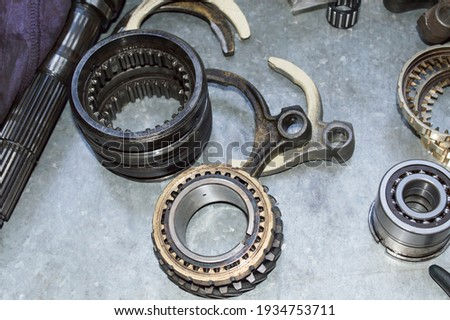 The gearshift forks and the elements of the synchronizer of the car's manual transmission lie on a metal worktable in the auto repair shop Stock photo ©