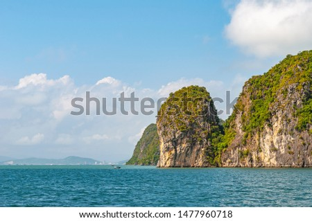 The geologic karst rock formations of Halong Bay in the South China Sea with the skyline of Haiphong city in the background, North Vietnam. #1477960718