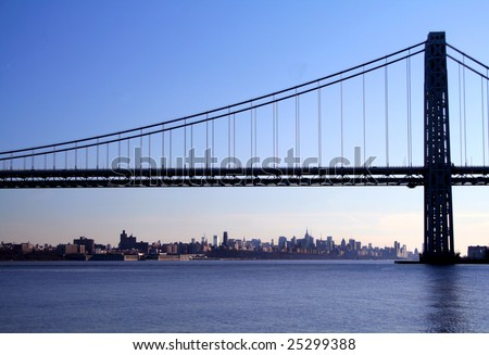 The George Washington Bridge crosses over the Hudson River from New Jersey to The Bronx, New York. New York Skyline in background.