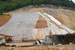 The geotextile fabric is spread over the surface of the slope to prevent erosion. Also to temporarily stabilize the slope before the permanent stabilization work done.