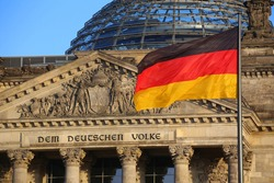 The German flag in front of the Reichstag building in Berlin. The inscription says: Dem Deutschen Volke - To the German people.