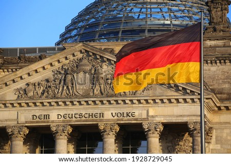 The German flag in front of the Reichstag building in Berlin. The inscription says: Dem Deutschen Volke - To the German people. Foto stock ©