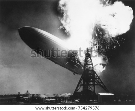 The German passenger airship Hindenburg seconds after catching fire, May 6, 1937. At 200 feet above the ground, flames erupt on top and in the back of the ship. It descended as it burned, reaching the - Shutterstock ID 754279576